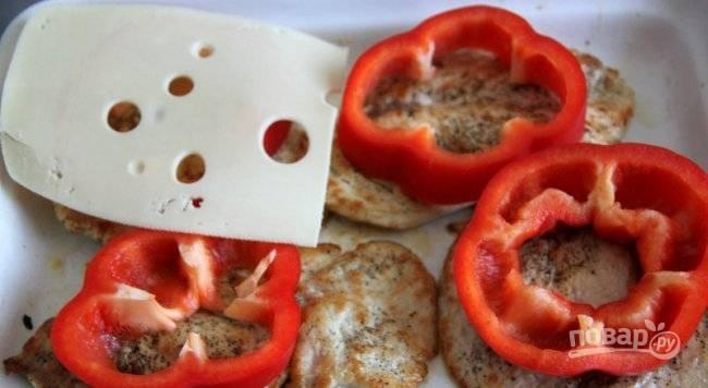 Отбивные переложите на противень. На каждый кусок уложите колечко перца и ломтик сыра. Запекайте блюдо в течение 10 минут при 180 градусах.