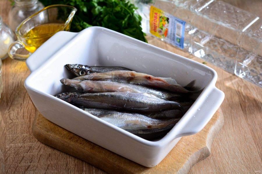 Промойте мойву и сложите в удобную емкость для маринования: контейнер, миску или кастрюлю.