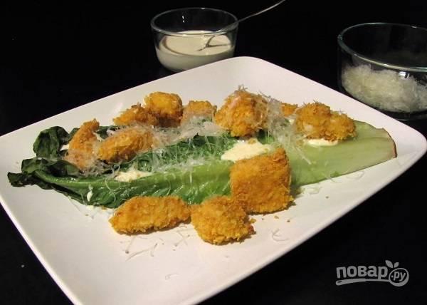 6. На тарелку для подачи выложите несколько листьев салата, курочку и присыпьте сверху тертым Пармезаном. Полейте заправкой и можно подавать к столу. Приятного аппетита!