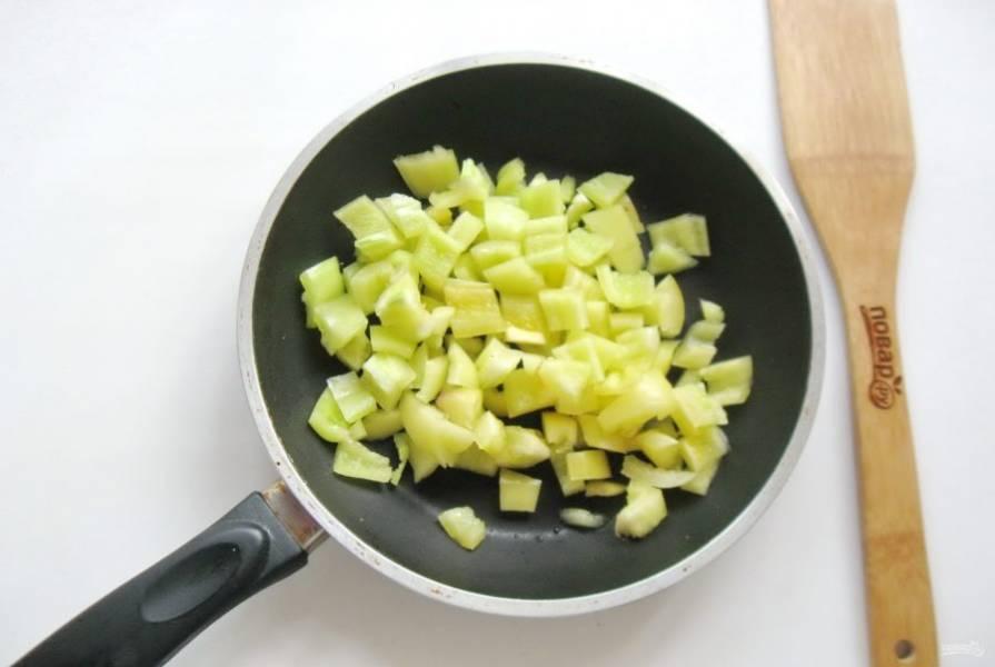 Болгарский перец помойте, удалите семенную коробочку и белые стенки внутри. Нарежьте небольшими кусочками и выложите в сковороду.