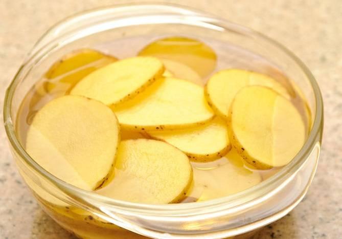 2. Если время позволяет, то залейте порезанный картофель водой и добавьте 3 столовые ложки соли. Оставьте на полчаса. Затем просушите. Если времени нет, то ничего и не делаем, посолим уже готовые чипсы.