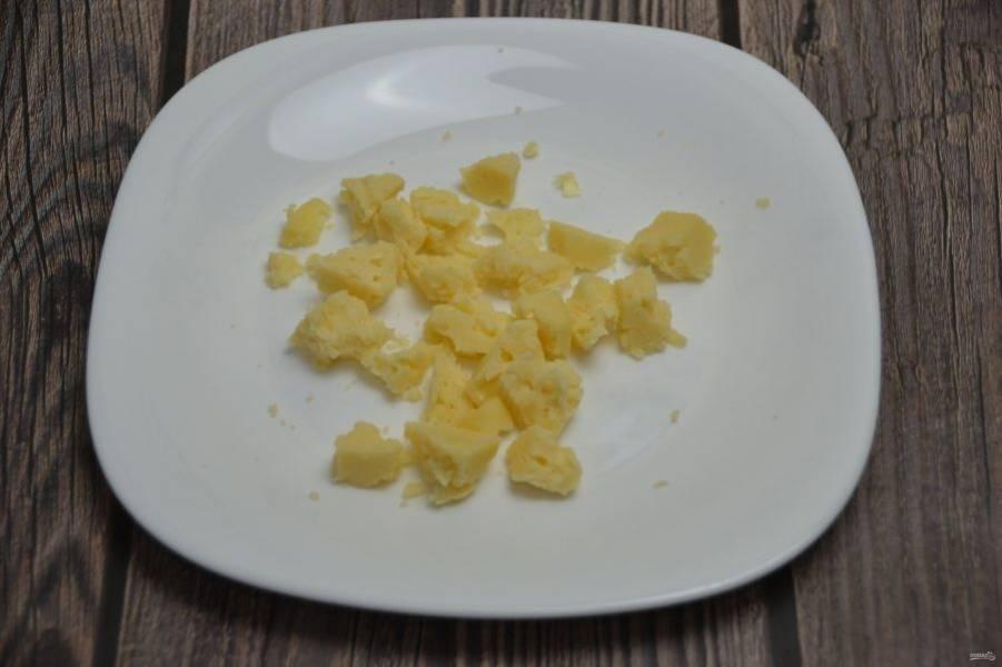 Поломайте руками сыр на небольшие кусочки.