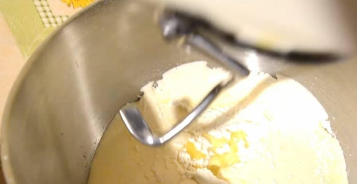 2.  Муку просейте с разрыхлителем и добавьте к яичной массе. Добавьте растопленное и слегка остывшее сливочное масло. Аккуратно перемешайте массу насадкой «крюк».