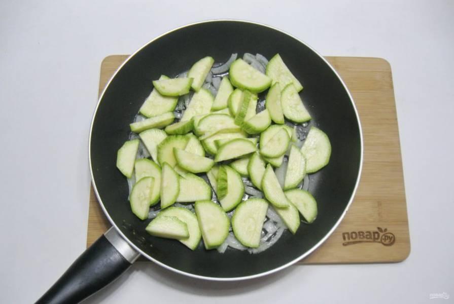 Кабачок помойте, обсушите и нарежьте половинками кружков. Добавьте к луку в сковороду.