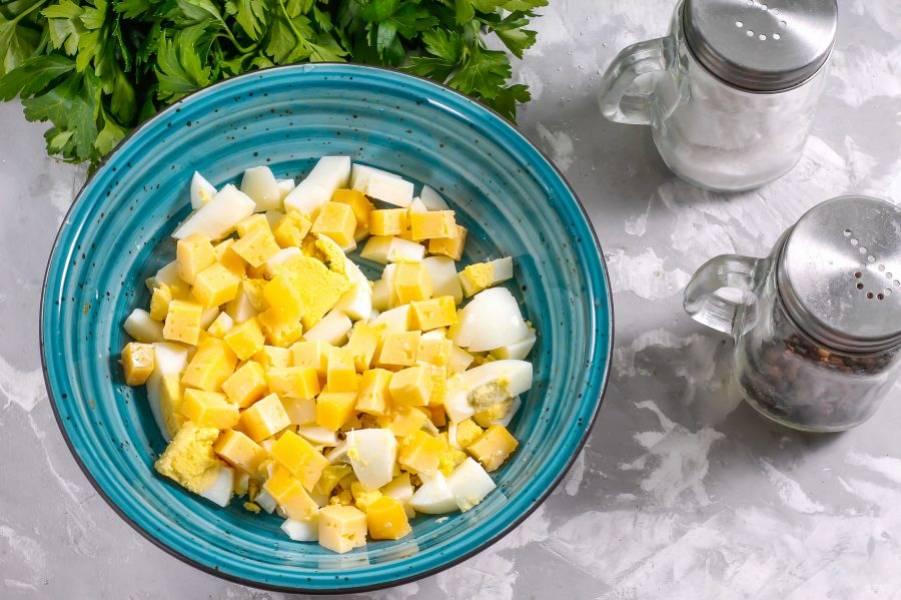 Твердый сыр любого, выбранного вами сорта, нарежьте средними по размеру кубиками и добавьте в емкость к отварным куриным яйцам.