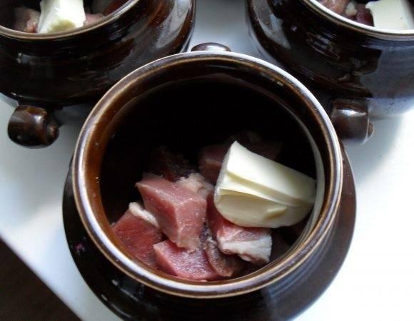 Нарезанное мясо выкладываем на дно горшочка, солим, перчим и добавляем кусочек сливочного масла.
