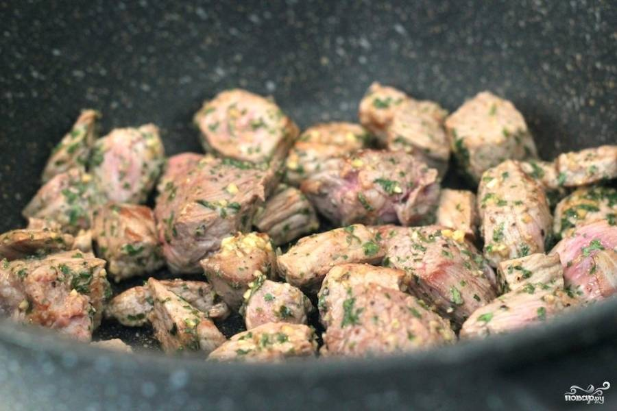 Теперь добавляем в сковороду измельченный чеснок и говядину. Обжариваем на быстром огне до коричневой корочки на кусочках говядины. Солим, перчим, добавляем петрушку.