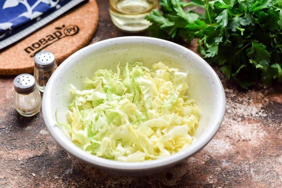 Возьмите молодую капусту, снимите верхние листья, после разрежьте вилок пополам. Нашинкуйте капусту тонкими полосками. Выложите капусту в салатник.