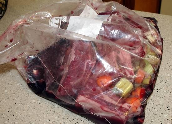 2. Сверху добавить лавровый лист, плотно завязать пакет. Отправить его в холодильник на 10-12 часов, чтобы мясо как следует промариновалось. Овощи в рецепте приготовления свиных ребрышек с подливкой можно использовать и другие по вкусу.