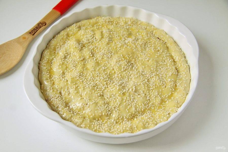 Любым удобным способом защипните края, сделайте по всей поверхности проколы вилкой и смажьте верх пирога яичным желтком. По желанию посыпьте кунжут. Выпекайте в духовке при температуре 180 градусов 30-40 минут или до образования румяного верха.