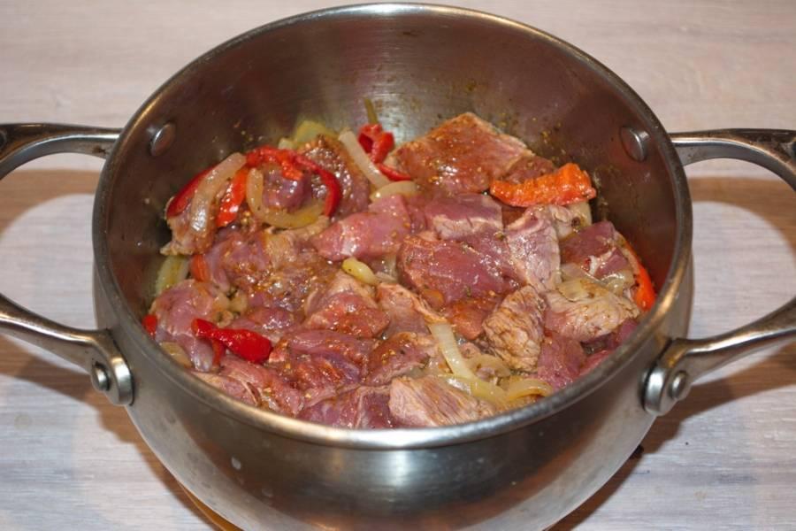 К овощам добавьте мясо.  К мясу сразу же добавьте специи. Перемешайте мясо с овощами и специями.