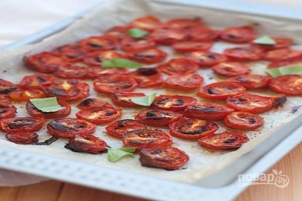 Приготовьте помидоры-конфи: разрежьте помидоры пополам, выложите на противень, покрытый бумагой для выпечки. Залейте помидоры приготовленной смесью и запекайте 45 минут при температуре 150 градусов.