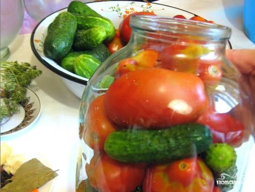 1. Хорошо моем огурцы с помидорами. В чистые банки выкладываем листья, потом все приправы и чеснок, затем огурцы и помидоры, аккуратно их чередуя.