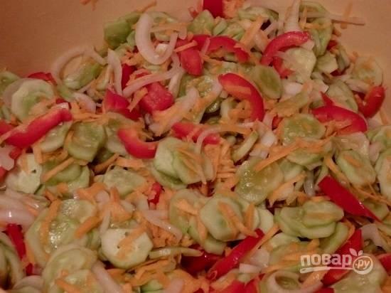 А пока очистим морковь и перец. Морковь натираем на крупной терке, перец нарезаем соломкой. Добавляем к огурцам морковь, перец и все остальные ингредиенты. Перемешиваем.