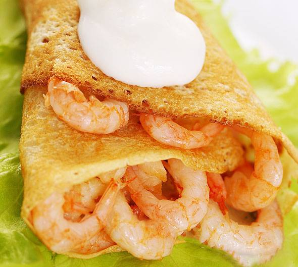 Блинчики выложите на тарелку воронкой или трубочками предварительно начинив их креветками. Блюдо готово! Приятного аппетита!
