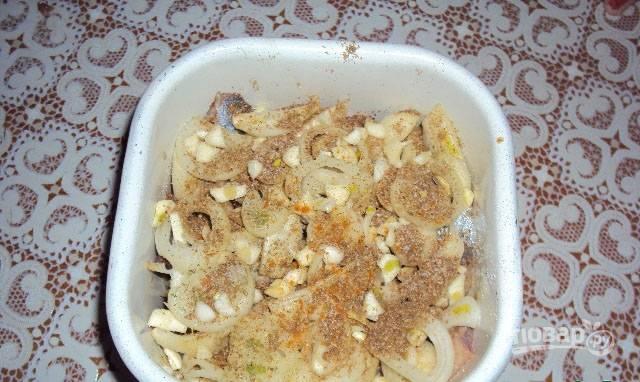 Посыпьте слоем нарезанного кольцами лука, приправьте перцем, кориандром и ломаным лавровым листом. Повторите слой сельди и лука со специями + рубленый чеснок.