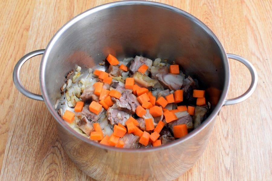 Добавьте мясо и кубики моркови. Жарьте, помешивая, 3-4 минуты.