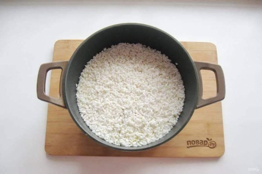 Выложите рис ровным слоем на курицу с морковью и луком. Немного посолите.