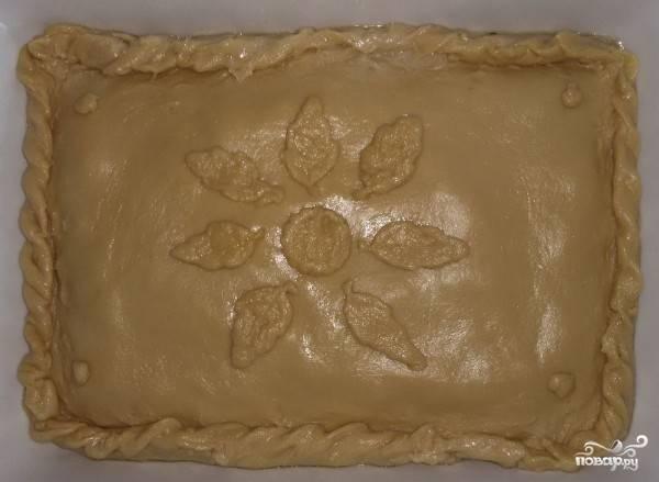 Форму, в которой будет выпекаться пирог, смажьте растительным маслом. Теперь на дно формы нужно выложить половину теста равномерным слоем. Я растягиваю тесто руками. Затем в форму выложите начинку, а второй частью теста накройте её. По желанию верхнюю часть можно украсить кусочками теста.