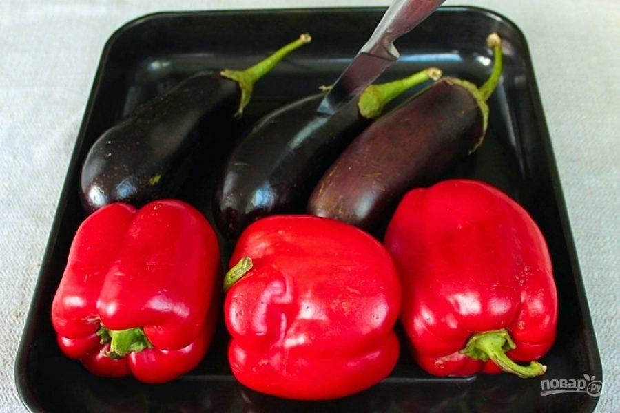 Баклажаны и крупный болгарский перец прокалываем и выкладываем на противень. Баклажаны кладем вглубь духовки, а перец ближе к дверце.