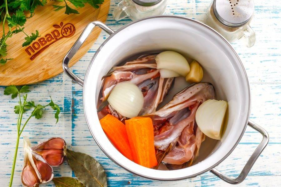 Выложите промытые щучьи головы в кастрюлю, туда же добавьте лук, морковь и чеснок.
