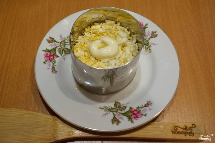 Смажьте помидорный слой майонезом. Теперь натрите на терке отварные яйца. Выложите их следующим слоем.