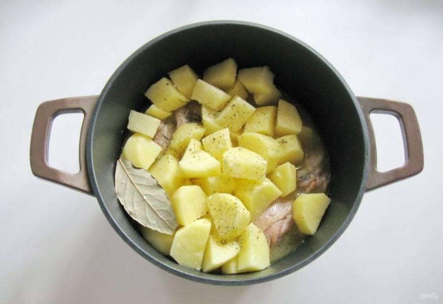 Картофель очистите, помойте и нарежьте кубиками, но не очень мелко. Выложите в кастрюлю к курице. Добавьте лавровый лист, соль, перец и любимые специи.