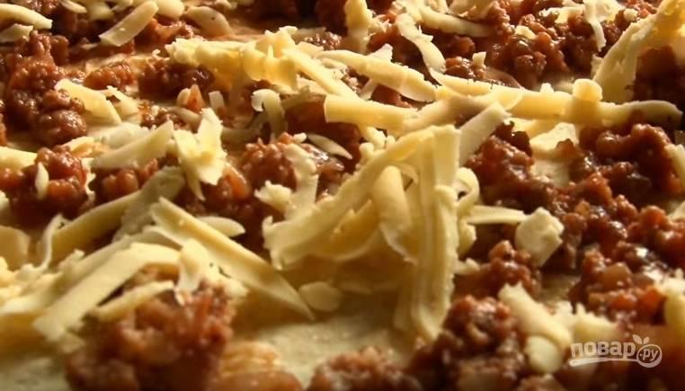 4. Выложите лаваш на стол, распределите по нему фарш и посыпьте половиной тертого сыра. Затем заверните лаваш в рулет.