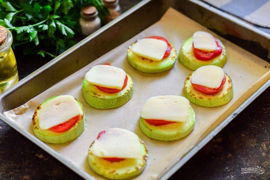 Сыр сулугуни нарежьте тонкими пластинами, выложите поверх помидоров. Запекайте кабачки в духовке при температуре 180 градусов 15-20 минут. Спустя время аппетитную закуску можно подавать к столу.