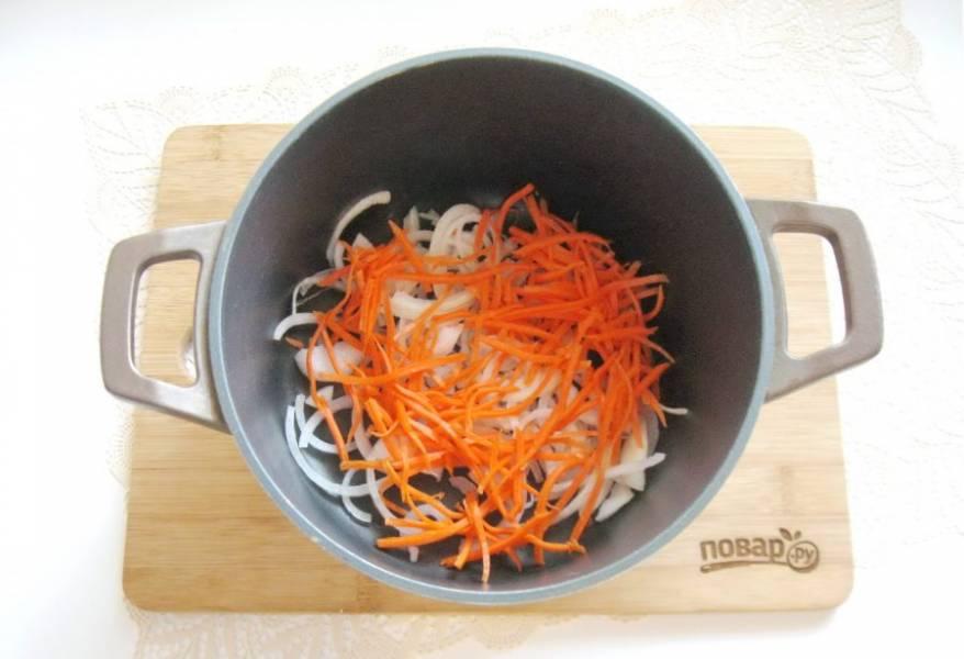 Морковь и лук очистите и помойте. Лук нарежьте полукольцами, а морковь соломкой. Выложите в кастрюлю с толстым дном. Налейте растительное масло и слегка обжарьте овощи, периодически перемешивая.