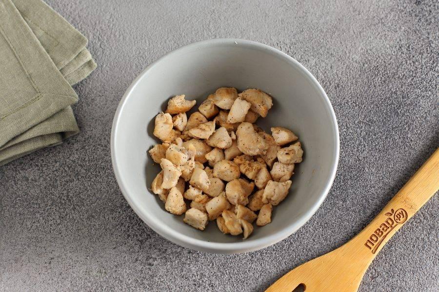 Куриное филе нарежьте небольшими кусочками, посолите, поперчите, обжарьте в сковороде и переложите в глубокую миску.