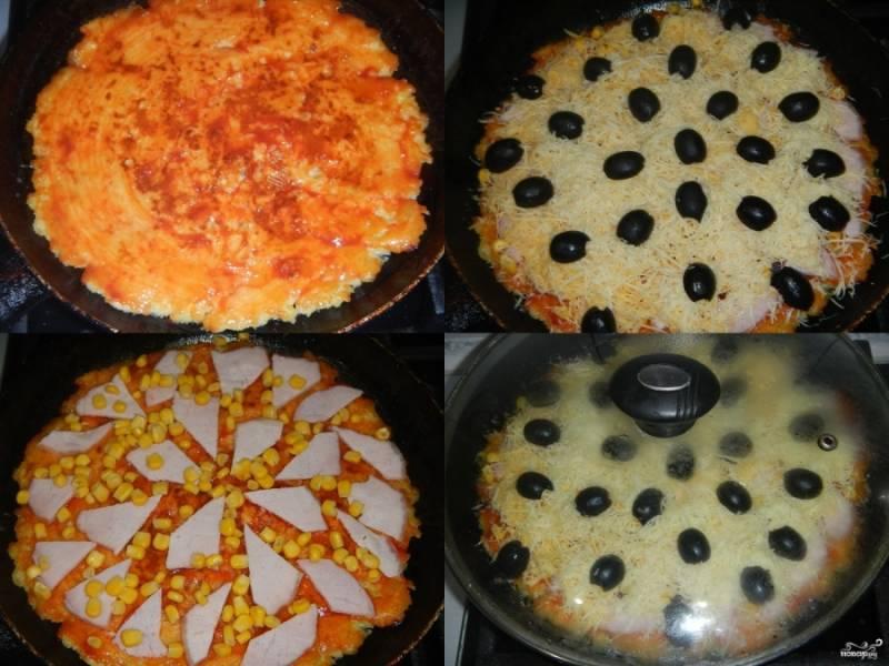4.Перевернутую основу для пиццы промажьте кетчупом, равномерно распределите на ней поочередно: балык, нарезанный тонкими ломтиками, кукурузу, тертый сыр и маслины. Сковороду снова поставьте на средний огонь, накройте крышкой. Сделайте огонь минимальным, готовьте, пока сыр не расплавится.