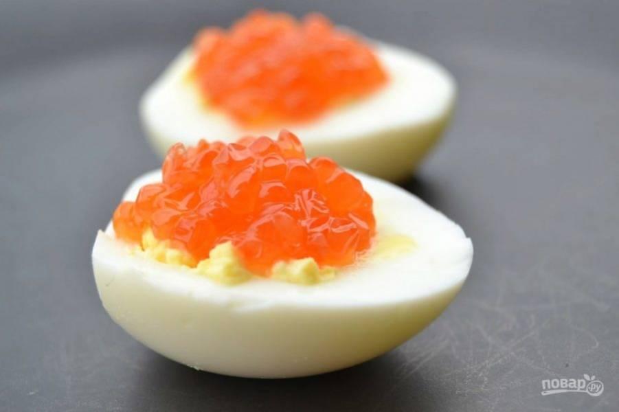 4.Выложите приготовленную начинку обратно в белковые половинки и украсьте икрой.
