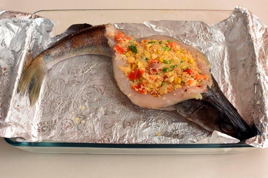 Уложите рыбу в форму или противень, застеленный фольгой. Наполните рыбу начинкой, формируя «лодочку». Смажьте размягченным сливочным маслом. Свободно накройте фольгой сверху.