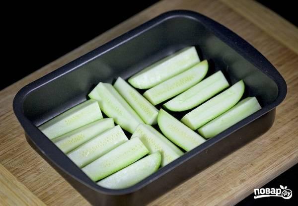 1. Сразу включите духовку, пусть разогревается до 200 градусов. Вымойте и обсушите кабачки. Нарежьте брусочками и выложите в жаропрочную форму.