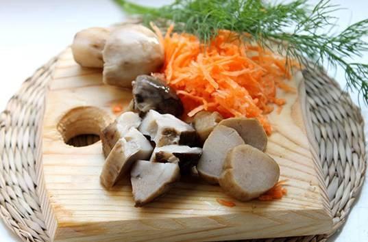 Морковь трем на терке, а маринованные грибочки измельчаем, выкладываем грибы в бульон к картофелю, солим суп и перчим его.