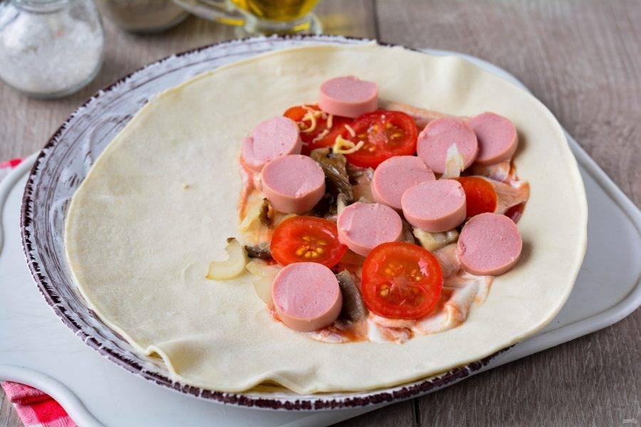 Одну половину теста смажьте майонезом и кетчупом, выложите начинку из грибов, колбасы и помидоров.