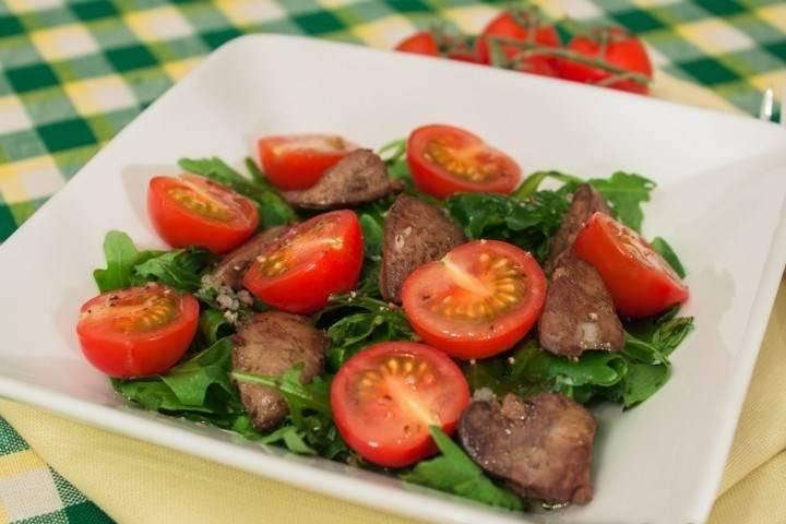 На порционные тарелки выкладываем листья салата, а поверх них - печень. Украшаем все это половинками помидорок. Заливаем сверху приготовленной заправкой. Приятного аппетита!