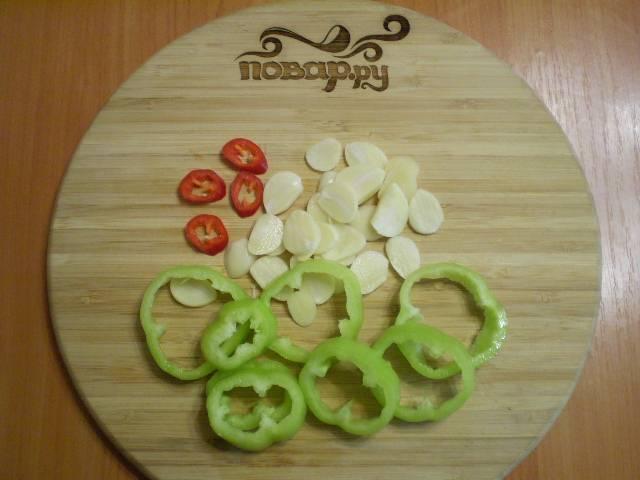 Порежьте перец, чеснок и чили.