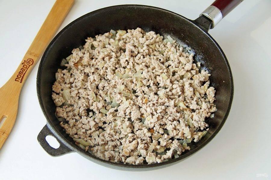 Тем временем приготовьте для начинки фарш. Разогрейте сковороду, налейте немного растительного масла и обжарьте до мягкости нарезанный кубиками лук. Добавьте к нему фарш, соль и перец по вкусу. Обжарьте все вместе еще несколько минут, до тех пор, пока фарш не побелеет. Комочки разбивайте лопаткой.