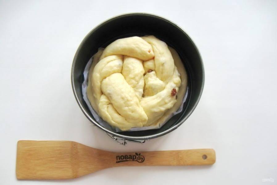 Косу сверните в круг и выложите на тесто в форме. Дайте будущему куличу постоять в тепле 40-50 минут. После смажьте желтком и отправьте в духовку, заранее разогретую до 175-180 градусов.
