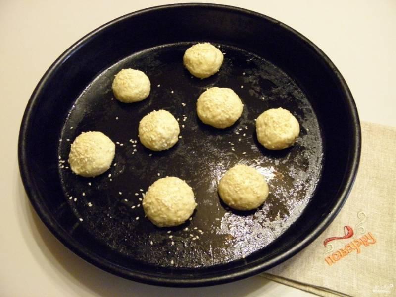 Смажьте противень маслом рафинированным или кулинарным жиром. Смажьте им же и руки, сформируйте шарики из теста. Посыпьте их кунжутом, к жирному тесту он отлично прилипает.
