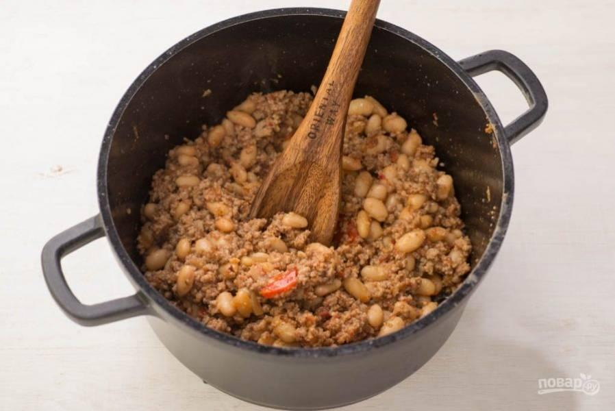 Добавьте в обжаренный фарш фасоль (можно вместе с жидкостью), томатный соус, перец, и соль.