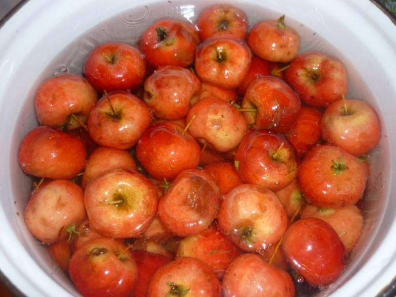 Отбираем яблочки, моем их. Отрезаем у них хвостики (не полностью, скорее просто немного подрезаем). Каждое яблочко теперь несколько раз протыкаем зубочисткой. Это нужно, чтобы при варке фрукты не полопались. Теперь вам понадобится кастрюля с водой (это не те 250 мл. воды, которые указаны в ингредиентах). Кастрюля должна вмещать в себя все яблоки, а воды должно быть столько, чтобы она покрывала фрукты. Доводим воду до кипения. Как только это случилось, забрасываем в неё яблоки на 5 минут. По прошествии этого времени яблоки сразу же нужно будет остудить под холодной водой.