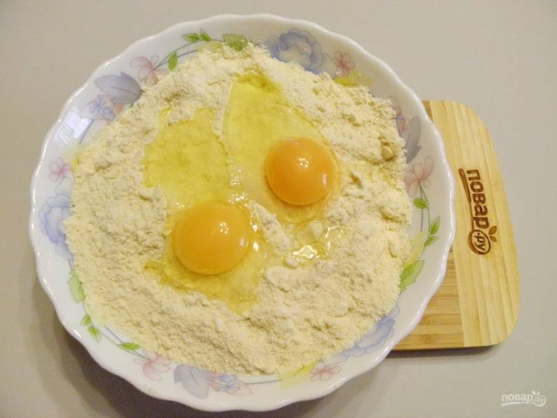 Добавьте два крупных яйца. Начинайте замешивать тесто. В начале может показаться, что это невозможно, но не переживайте, тесто за 10-12 минут замеса отлично собирается в ком.