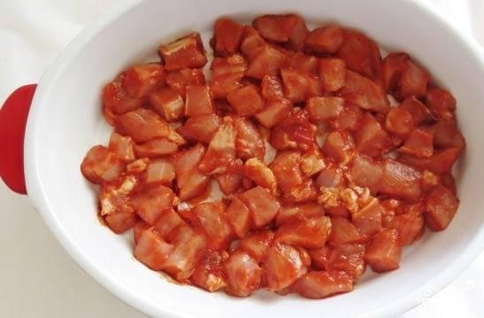 Мякоть свинины вымойте, зачистите от лишнего жира, пленок и жилок. Затем нарежьте его на кубики. Выложите мясо в мисочку, посолите, добавьте специи по вкусу. Затем положите томатную пасту и хорошенько все размешайте. Оставьте мясо мариноваться на пару часов в холодильнике.