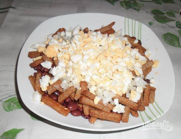 Яйцо отварите вкрутую. Остудите его, очистите от скорлупы и нарежьте кубиками. Добавьте их к салату.