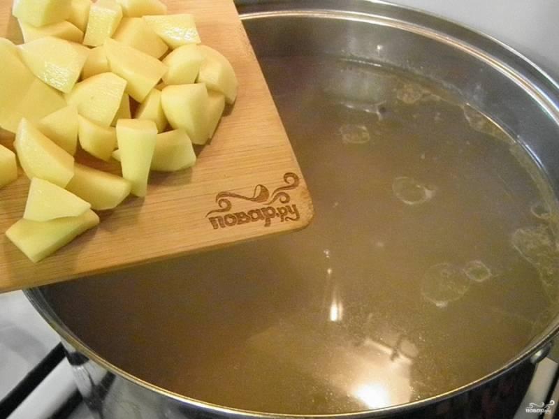 Когда бульон будет готов, достаньте из него косточки, а мясо верните в суп. Добавьте не крупно порезанный картофель, проварите 20 минут.