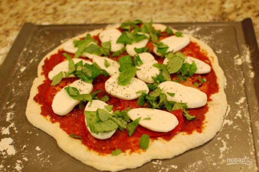 8.Нарежьте кружочками помидор, выложите его, а затем кусочки моцареллы и зелень на тесто, поперчите немного.