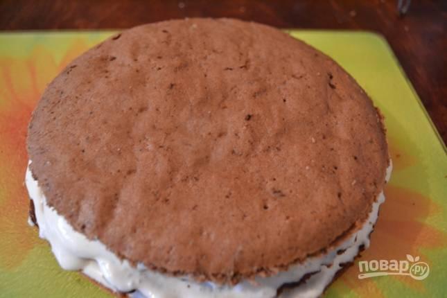 Следующий корж шоколадный. Тоже смазываем его кремом и посыпаем орехами. И продолжаем чередовать коржи и смазывать их кремом.